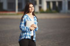 Junge lächelnde Studentenfrau mit Büchern in den Händen, die im Freien stehen stockbilder