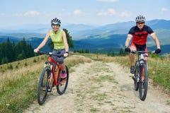 Junge lächelnde Touristen verbinden Mann und Frau in Radfahrenfahrrädern der Berufssportkleidung unten stockbilder