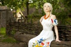 Junge ländliche Frau, die auf der alten Holzbank sitzt Lizenzfreies Stockfoto
