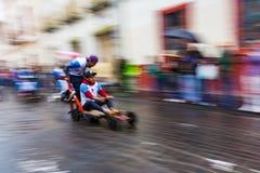Junge läuft hinunter Straße im selbst gemachten Fahrzeug während des Seifenkistenrennens Lizenzfreies Stockfoto