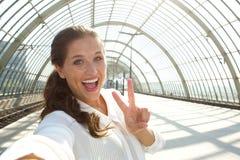 Junge lachende Frau, die selfie mit Friedenszeichen nimmt Stockfotografie