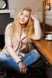 Junge langhaarige Blondine im Café Lizenzfreies Stockbild