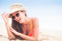 Junge langhaarige Frau in der Sonnenbrille und im Bikini lächelnd und durch den Strand ein Sonnenbad nehmend Lizenzfreies Stockfoto