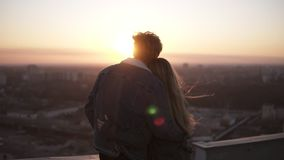Junge langhaarige Frau und Mann, welche die Stadt bei dem Sonnenuntergang steht auf dem Dach des hohen Gebäudes betrachtet Aufpas stock video footage
