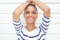 Junge lateinamerikanische Frau, die auf weißem Hintergrund lächelt Stockfotos