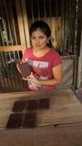 Junge lateinische Frau, die einen Block der handgemachten Schokolade in ihrer Hand hält Lizenzfreie Stockfotos