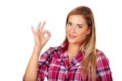Junge lächelnde Frau, die perfektes Zeichen gestikuliert Lizenzfreie Stockfotografie