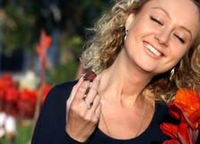 Junge lächelnde Frau, die Schokolade isst Lizenzfreies Stockbild