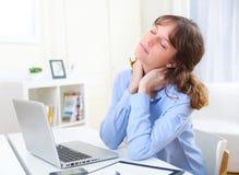 Junge lächelnde Geschäftsfrau, die bei der Arbeit sich entspannt Lizenzfreie Stockbilder