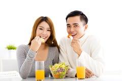 Junge lächelnde Paare, die gesundes Lebensmittel essen Stockfotos