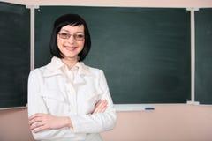 Junge Lehrerfrau auf grünem Vorstand stockfotografie
