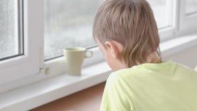 Junge lernt, die Briefe zu schreiben, die durch die Tabelle sitzen Handeln von Hausarbeit mit Lehrertutor stock video