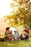 Junge Leute auf dem Camping-Ausflug zu spielen und zu singen lizenzfreie stockfotografie