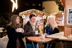 Junge Leute auf einem Weihnachtsmarkt Stockbild