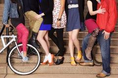 7 junge Leute auf Treppe, mit einem Fahrrad Stockbild