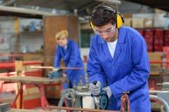 Junge Leute bei der Arbeit in der Fabrik stockbild
