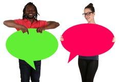 Junge Leute bemannen die Frau, die leere Spracheblasen mit copyspa hält Stockfotos