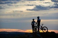 Junge Leute der hinteren Ansicht zwei mit Mountainbiken stehen auf Klippe mit schöner Landschaft bei Sonnenuntergang stockfotografie