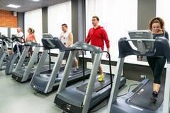 Junge Leute, die Übungen in der Turnhalle tun Stockbild