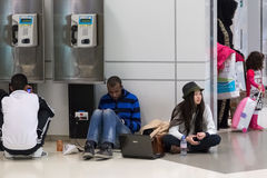 Junge Leute, die auf dem Boden sitzen und auf ihren Flug an internationalem Flughafen Dohas warten Lizenzfreie Stockfotografie
