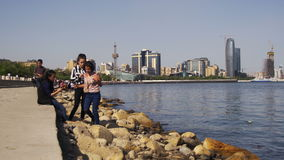 Junge Leute, die auf dem Damm von Baku nahe dem Kaspischen Meer, Aserbaidschan stillstehen stock video