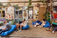 Junge Leute, die Café am im Freien mit aufblasbaren Stühlen im untersetzten Bereich sich entspannen Stockbilder
