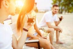 Junge Leute, die das ein Sonnenbad nehmende Trinken der Sommerferien an der Strandbar genießen stockbild