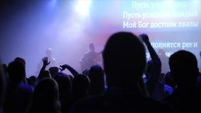 Junge Leute, die das Konzert genießen Einige von ihnen Sprung, einige stehen zujubeln Blaue Leuchte Rückseitige Ansicht stock video