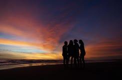 Junge Leute, die den Sonnenuntergang genießen Lizenzfreie Stockbilder