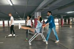 Junge Leute, die den Spaß, laufend auf Einkaufslaufkatze am Parken haben lizenzfreies stockbild