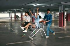 Junge Leute, die den Spaß, laufend auf Einkaufslaufkatze am Parken haben lizenzfreies stockfoto