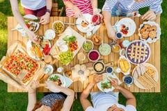Junge Leute, die draußen essen stockbild
