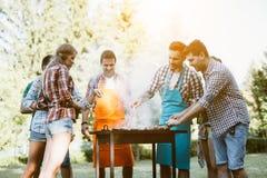 Junge Leute, die draußen grillen lizenzfreie stockfotografie
