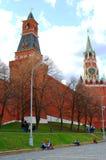 Junge Leute, die durch die Wand Moskaus der Kreml sitzen Stockbilder