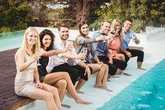 Junge Leute, die durch Swimmingpool sitzen Lizenzfreies Stockbild