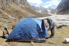Junge Leute, die ein Zelt auf einem Berg errichten Stockbild