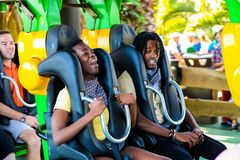 Junge Leute, die eine Achterbahn an einem Freizeitpark reiten Lizenzfreie Stockfotos