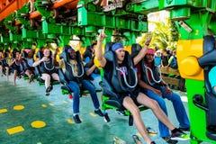 Junge Leute, die eine Achterbahn an einem Freizeitpark reiten Lizenzfreie Stockbilder