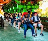 Junge Leute, die eine Achterbahn an einem Freizeitpark reiten Stockfotografie