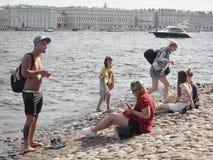 Junge Leute, die an einem sonnigen Tag auf den Banken des Flusses Neva in St Petersburg sich entspannen Russland Der Sommer von 2 Stockbild