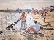Junge Leute, die an einem sonnigen Tag auf den Banken des Flusses Neva in St Petersburg sich entspannen Russland Der Sommer von 2 Lizenzfreies Stockfoto