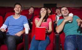Junge Leute, die einen Film am Kino aufpassen stockfotos