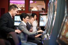 Junge Leute, die im Kasino auf Spielautomaten spielen Lizenzfreie Stockfotografie