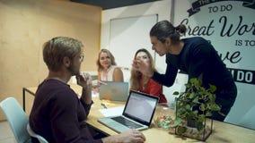 Junge Leute, die intensiv Pläne am Debattentisch besprechen Analysetagesgeschäftunternehmenspläne stock video