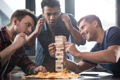 Junge Leute, die jenga Spiel spielen Lizenzfreie Stockfotografie