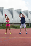 Junge Leute, die Kessel-Bell-Übung im Freien tun Stockbilder