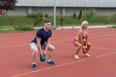 Junge Leute, die Kessel-Bell-Übung im Freien tun Stockbild