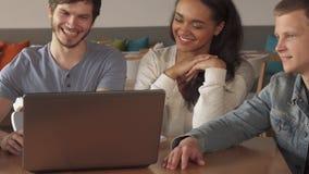 Junge Leute, die lächeln über, was sie auf Laptop am Café sehen stock video footage