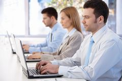 Junge Leute, die an Laptop im Konferenzzimmer arbeiten Stockfoto