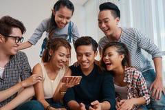 Junge Leute, die lustige Videos aufpassen lizenzfreie stockfotos